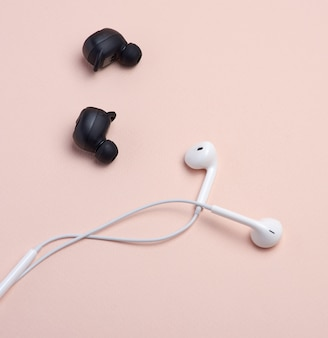 Black wireless and white earphones with wire