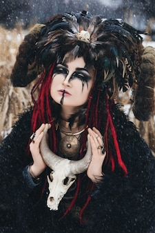 Black witch in a crown with horns and feathers in a black fur cape in a snow storm