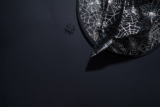 Black witch hat with a pattern of cobwebs on black background