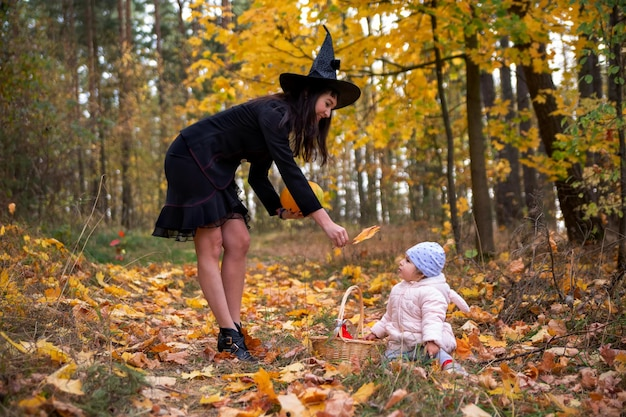 Black witch with little toddler bunny in the autumn forest halloween celebration costume party