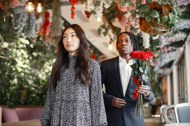 Black with dreadlocks. girl in a festive dress. bouquet of red roses.