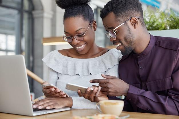 Черная женщина и мужчина проводят неформальную встречу, рады просматривать фотографии на смартфоне, носить очки, вместе работать над общим проектом через портативный компьютер.