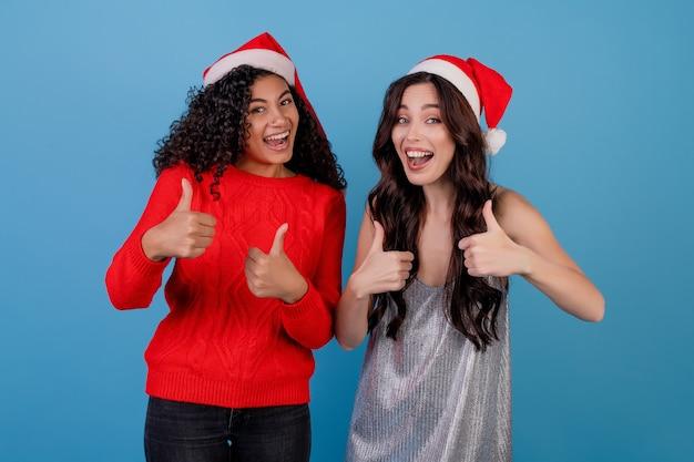 흑인 여자와 백인 여자 엄지 손가락을 보여주는 블루 위로 절연 크리스마스 모자를 쓰고
