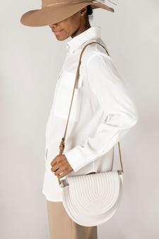 白い織り綿ロープバッグのモックアップを運ぶ黒人女性
