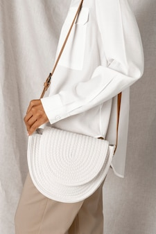 Black woman carrying a white woven cotton rope bag