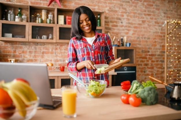 Черная женщина готовит салат на кухне