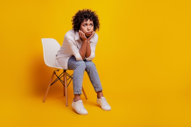 울고 있는 흑인 여성은 우울증이 노란 벽에 의자에 앉아 있다