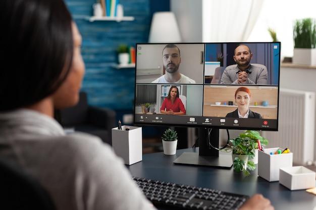 オンラインウェビナーのビデオ通話中に、学校のプロジェクトの期限についてリモートの同僚と話し合う黒人女性...