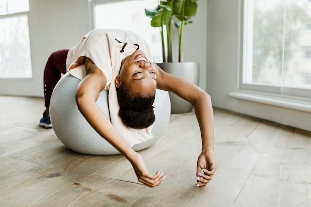 균형 공에 스트레칭을 하는 흑인 여성