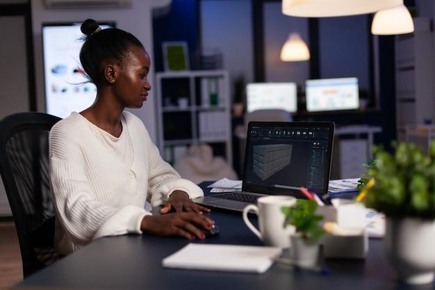 프로토타입을 위해 신생 회사에서 초과 근무하는 컨테이너의 3d 개념을 설계하기 위해 새로운 소프트웨어를 사용하여 랩톱 분석 프로젝트를 보고 있는 흑인 여성 엔지니어 디자이너