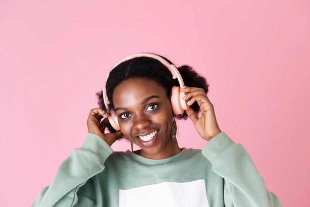 ピンクの背景で音楽を楽しんでいる黒人女性