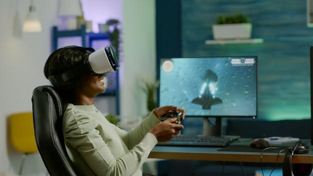 Vrヘッドセットを身に着けている夜遅くに強力なコンピューターでビデオゲームをプレイする黒人女性ゲーマー。自宅で仮想トーナメントゲームスペースシューターにワイヤレスコントローラーを使用する興奮したプレーヤー