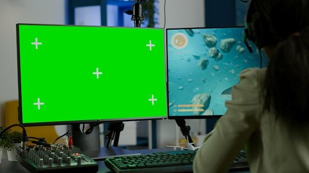 緑色の画面のモックアップクロマキーディスプレイを備えた強力なコンピューターでオンラインビデオゲームをストリーミングしている黒人女性ゲーマー。ヘッドセットでシューティングゲームをプレイする分離されたデスクトップでプロのpcを使用するサイバープレーヤー