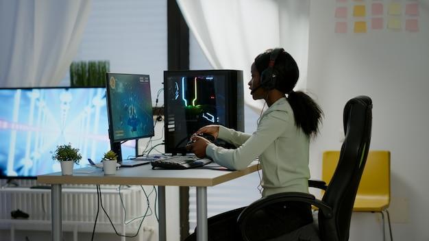 강력한 컴퓨터에서 전문 무선 컨트롤러와 헤드셋을 사용하여 비디오 게임에서 승리한 흑인 여성 게이머. 조이스틱을 사용하여 게임 토너먼트 중 공연하는 흥분된 온라인 스트리밍 사이버.