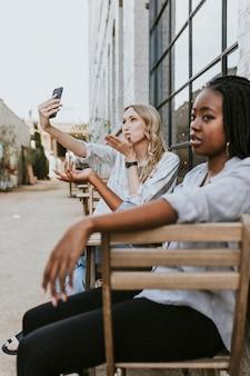 Чернокожей женщине надоедает ее подруга-блондинка, которая продолжает делать селфи