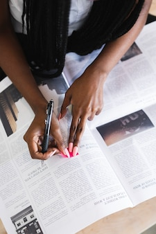 Black woman highlighting an article on the newspaper