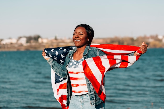 Black woman holding american flag leaning against back