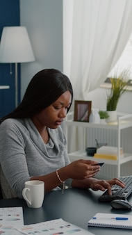 Black woman holding electronic credit card typing online payment on computer keyboard while ordering...