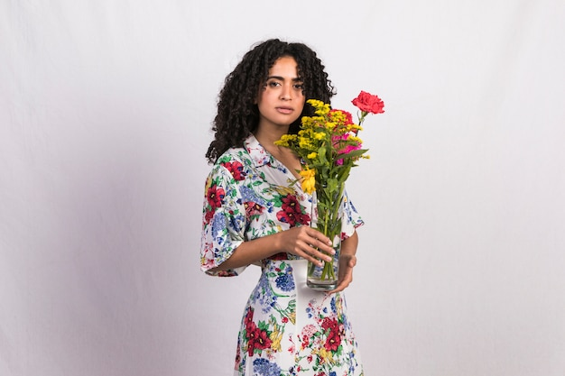 Black woman holding vase with flowers