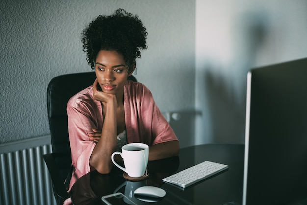 Black woman at home working with computer and coffee in the morning