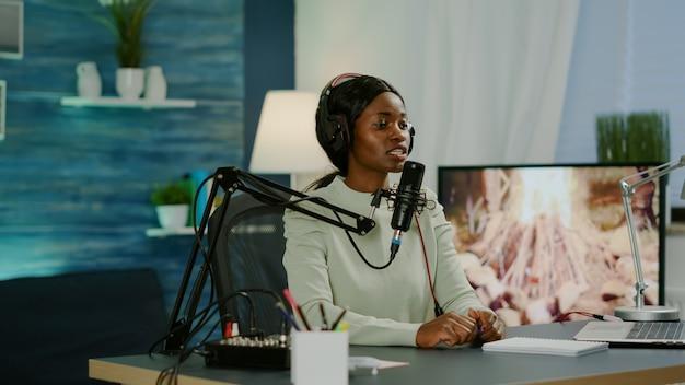 Ospite di una donna nera di uno spettacolo online che guarda nel computer portatile che parla nel microfono del podcast con l'intrattenimento degli ascoltatori. parlando durante il live streaming, blogger discutendo nel vlog indossando le cuffie.