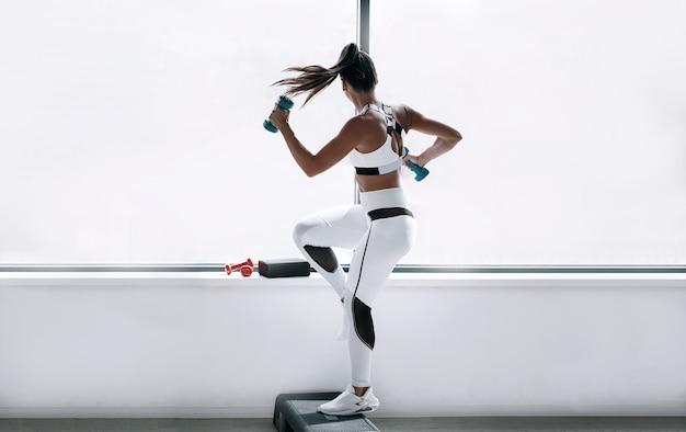 Черная женщина в белом спортивном костюме в тренажерном зале с гантелями в руках