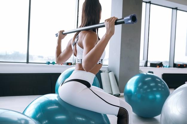 Черная женщина в отличной спортивной форме разогревает мышцы перед тренировкой на спортивном инвентаре