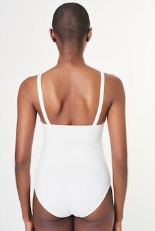 Черная женщина в белом сплошном купальнике, вид сзади