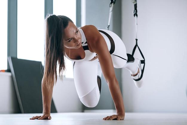 Черная женщина в белом спортивном костюме в тренажерном зале. черная женщина делает упражнения кроссфит