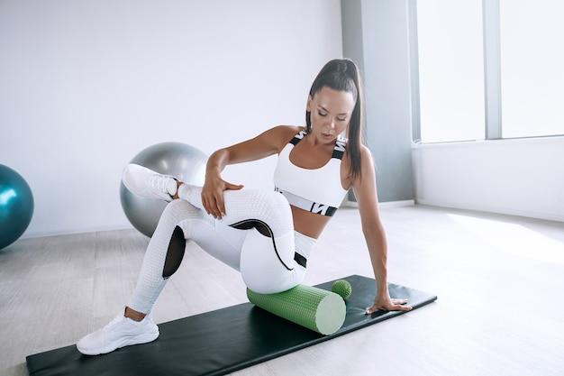 Черная женщина в белом спортивном костюме в тренажерном зале. черная женщина выступает на спортивном ролике