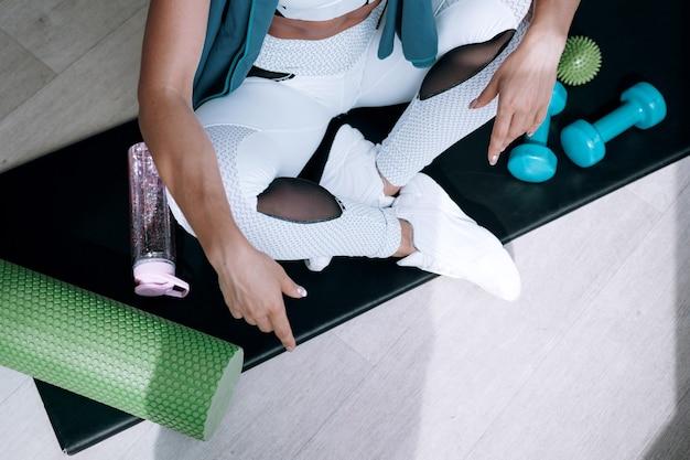 Черная женщина в белом спортивном костюме в тренажерном зале. черная женщина сидит на коврике в окружении спортивного снаряжения для кроссфита