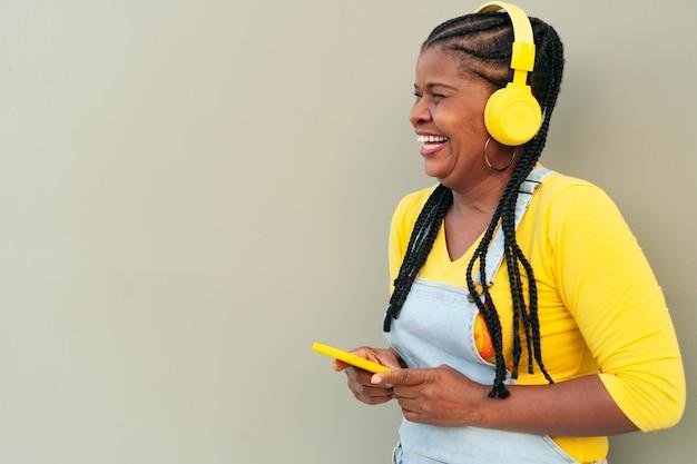 屋外でスマートフォンで音楽を聴いている黒人女性。