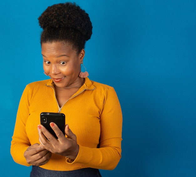 파란색 벽으로 그녀의 손에 핸드폰을보고 흑인 여성