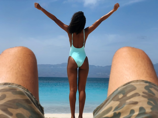 Black woman looking away on beach with open arms