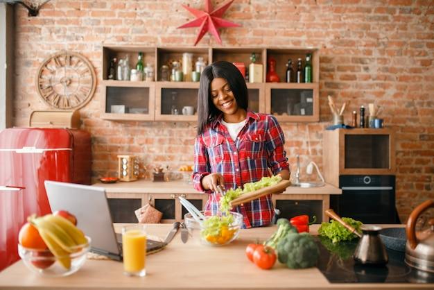 Черная женщина ищет рецепт на ноутбуке