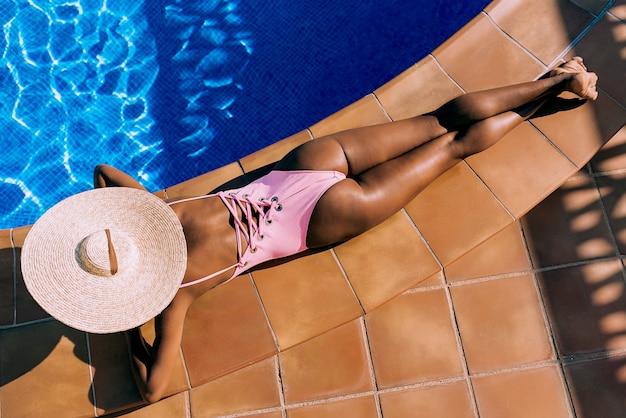 Чернокожая женщина лежа в стороне бассейна