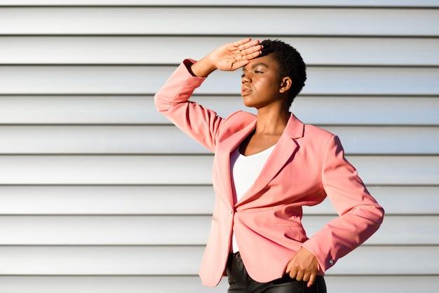 Black woman, model of fashion, standing on urban wall