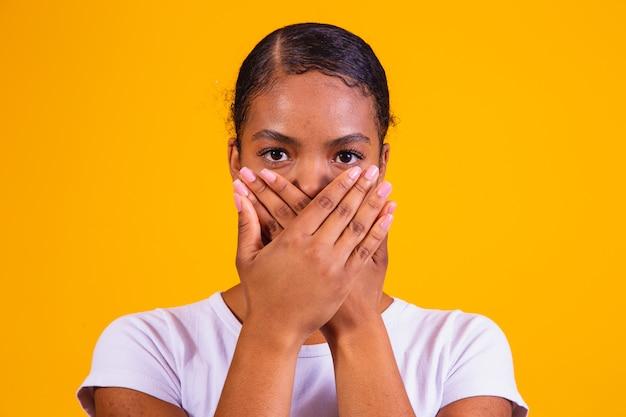 그녀의 입으로 노란색 배경에 흑인 여성은 침묵에 닫힙니다. 편견, 학대 및 인종 차별의 개념