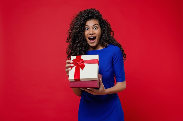 Black woman opening present box wearing blue dress isolated on red wall