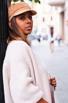 Черная женщина позирует на улице с осенней одеждой