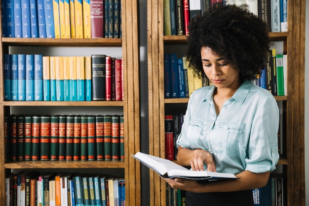 Black woman reading book in library