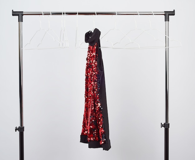 Black woman's clothing with red sequins hanging on a white iron hanger