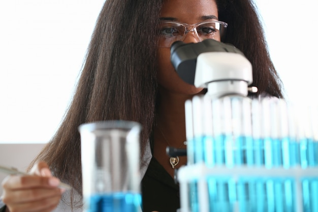 Black woman scientist student chemist in protective glasses