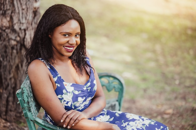 公園のベンチに一人で座っている黒人女性、リラックスして公園に座っているかなり浅黒い肌の女性。人、感情、ライフスタイルのコンセプト。