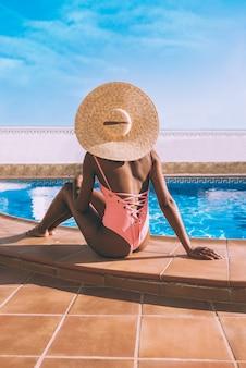 Чернокожая женщина, сидящая внизу у бассейна