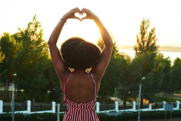 彼女の背中で心臓の立場を示す黒人女性