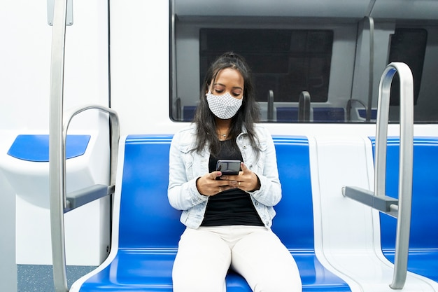 Black woman sitting alone in the subway car using a smartphone.