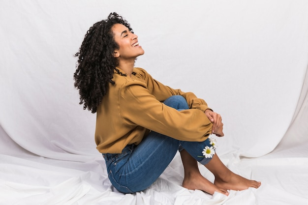 Black woman sitting with daisy flowers in jeans cuffs