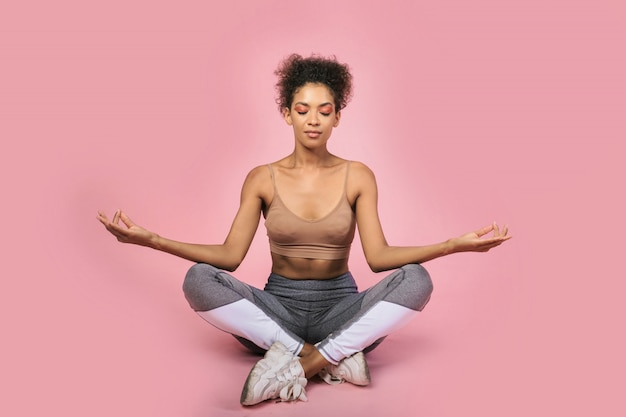 Black woman  sitting in yoga acana on pink background. healthy lifestyle concept. copispace.