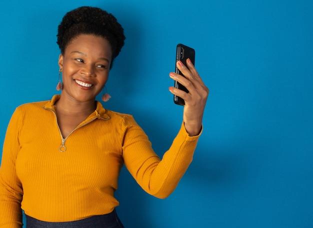 흑인 여성이 웃고 파란색 벽으로 핸드폰을 들고